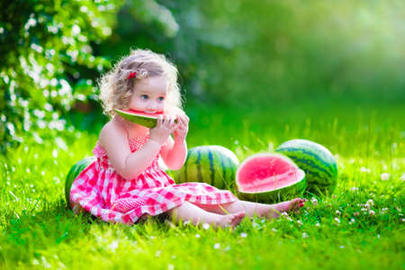 Foto de Child eating watermelon in the garden. Kids eat fruit outdoors. Healthy snack for children. Little girl playing in the garden holding a slice of water melon. Kid gardening. - Imagen libre de derechos