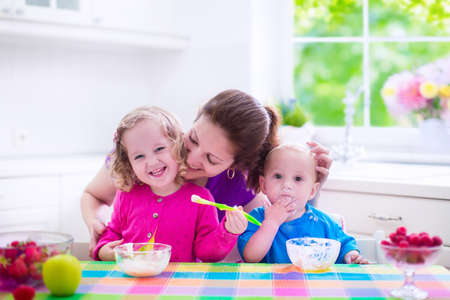 Photo for Family having breakfast in a white sunny kitchen. Young mother feeding two kids, eating fruit and dairy. Healthy nutrition for children - yogurt, strawberry and apple. Parent with toddler kid and baby cooking morning meal. - Royalty Free Image