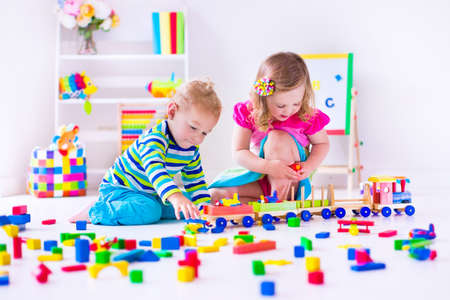 Foto de Kids play at day care. Two toddler children build tower of colorful wooden blocks. Child playing with toy train. Educational toys for preschool and kindergarten. - Imagen libre de derechos
