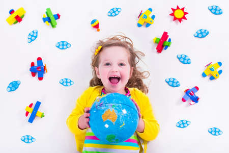 Foto de Child playing with wooden airplanes. Preschooler kid flying around the world. Kids travelling and playing. Children at day care or kindergarten. View from above. - Imagen libre de derechos