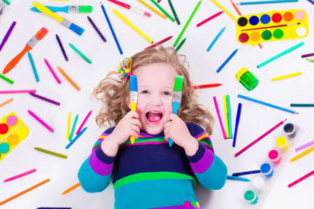 Foto de Child with draw and paint supplies. Kids happy to go back to school. Preschool kid learning and studying. Creative children at kindergarten. Office and art supply objects collection. - Imagen libre de derechos