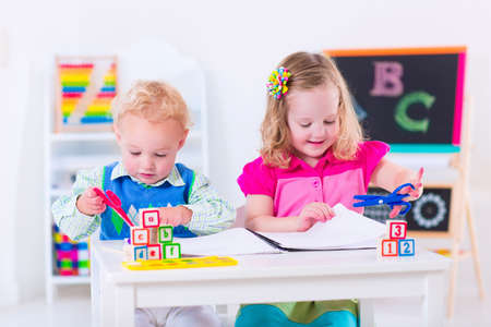 Photo pour Kids at preschool. Two children drawing and painting at kindergarten. Boy and girl happy to go back to school. Toddler kid and baby learn letters at child care. Class room with chalkboard and abacus - image libre de droit