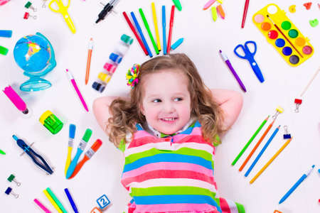 Foto de Child with draw and paint supplies. Kids happy to go back to school. Preschool kid learning and studying. Creative children at kindergarten. Office supply objects collection. - Imagen libre de derechos