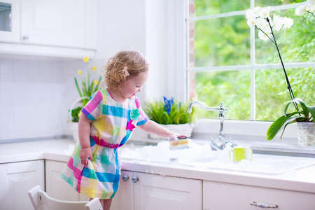 Foto de Child washing dishes. Kids wash plates and cups. Little girl helping in the kitchen playing with water and foam in a white sink with retro tap. Chores for children. Modern home interior with window. - Imagen libre de derechos