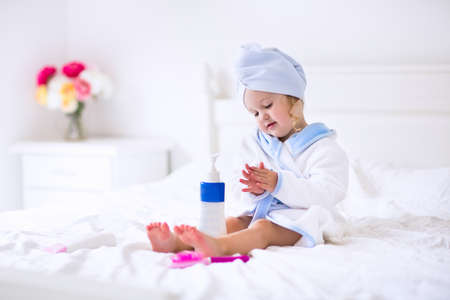 Foto de Child after bath. Cute little girl with wet curly hair wearing a bathrobe and head towel sitting on a white bed using lotion and brush. Hygiene for kids. Bathroom textile for babies and children. - Imagen libre de derechos