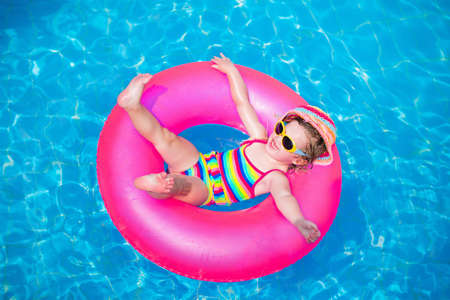 Foto de Child in swimming pool. Little girl playing in water. Vacation and traveling with kids. Children play outdoors in summer. Kid with inflatable ring toy. Swim wear and sun glasses for UV protection. - Imagen libre de derechos