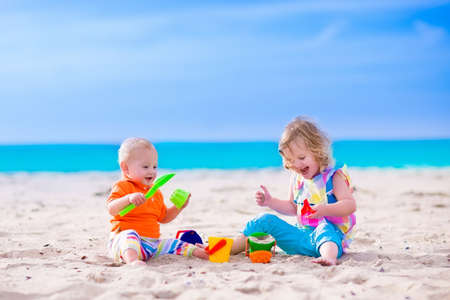 Photo pour Kids play on a beach. Children building sand castle on tropical island. Summer water fun for family. Boy and girl with toy buckets and spade at the sea shore. Ocean vacation with baby and toddler kid. - image libre de droit