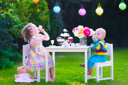 Foto de Garden birthday party for children. Kids outdoor celebration. Little boy and girl drinking tea and eating cake playing in the backyard in summer. Toddler and baby play with toy dishes and eat cupcakes - Imagen libre de derechos