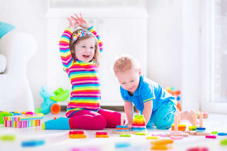 Foto de Preschooler child playing with colorful toy blocks. Kids play with educational wooden toys at kindergarten or day care. Preschool children build tower with wood block. Toddler kid in nursery. - Imagen libre de derechos