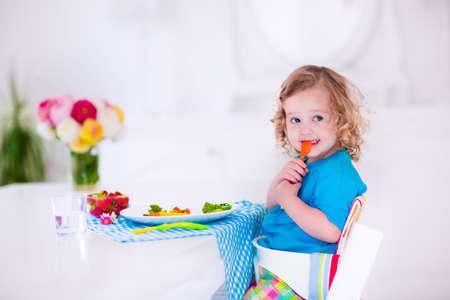 Foto de Child having vegetables for lunch. Healthy fruit and vegetable meal for children. Kids eat in a white dining room or kitchen. Toddler kid having breakfast. Food for preschooler at home or daycare. - Imagen libre de derechos