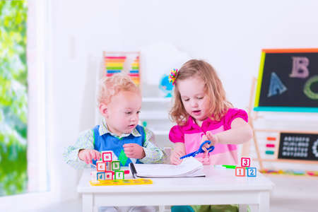 Kids at preschool. Two children drawing and painting at kindergarten. Boy and girl happy to go back to school. Toddler kid and baby learn letters at child care. Class room with chalkboard and abacus