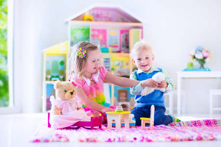 Foto de Kids playing with doll house and stuffed animal toys. Children sit on a pink rug in a play room at home or kindergarten. Toddler kid and baby with plush toy and dolls. Birthday party for little child. - Imagen libre de derechos