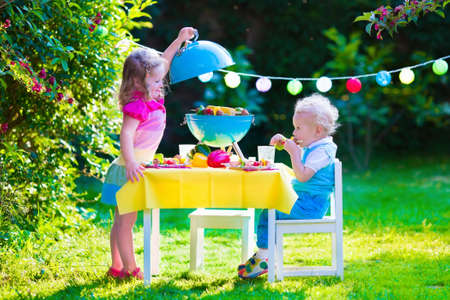 Foto de Children grilling meat. Family camping and enjoying BBQ. Brother and sister at barbecue preparing steaks and sausages. Kids eating grill and healthy vegetable meal outdoors. Garden party for child. - Imagen libre de derechos