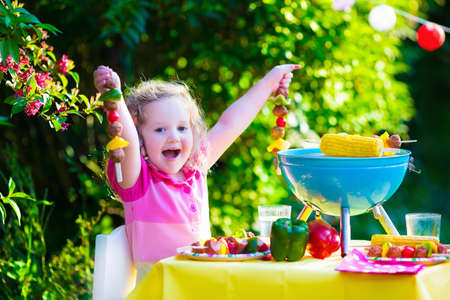 Foto de Children grilling meat. Family camping and enjoying BBQ. Little girl at barbecue preparing steaks kebab and corn. Kids eating grill and healthy vegetable meal outdoors. Garden party for toddler child - Imagen libre de derechos