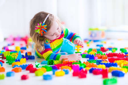 Foto de Preschooler child playing with colorful toy blocks. Kids play with educational toys at kindergarten or day care. Preschool children build tower with plastic block. Toddler kid in nursery. - Imagen libre de derechos