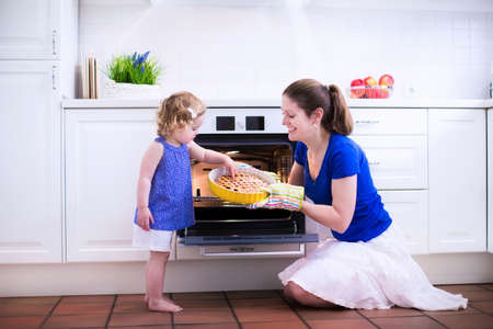 Photo pour Mother and child bake a pie. Young woman and her daughter cook in a white kitchen. Kids baking pastry. Children helping to make dinner. Modern interior with oven and other appliances. Family eating. - image libre de droit