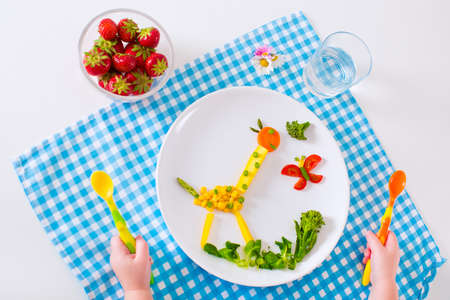 Foto de Healthy vegetarian lunch for little kids. Kid meal. Vegetable and fruit served as animals corn broccoli carrot strawberry helping child to learn eating right and clean children hands with spoon - Imagen libre de derechos