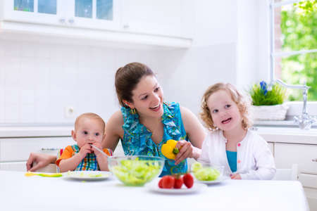 Photo pour Young mother and two children cooking in a kitchen. Parent and kids cook dinner. Family with baby and toddler kid eat at home. Child preparing and eating vegetable lunch. Preschooler healthy nutrition - image libre de droit