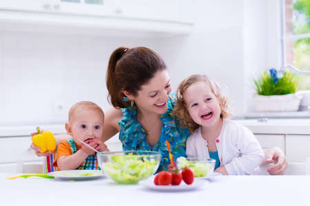 Foto de Young mother and two children cooking in a kitchen. Parent and kids cook dinner. Family with baby and toddler kid eat at home. Child preparing and eating vegetable lunch. Preschooler healthy nutrition - Imagen libre de derechos