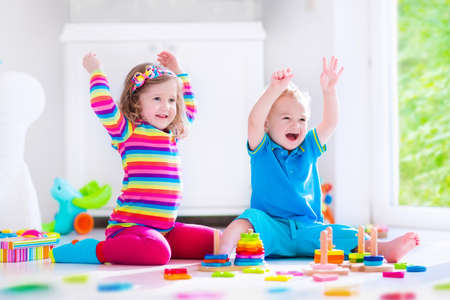 Foto de Preschooler child playing with colorful toy blocks. Kids play with educational wooden toys at kindergarten or day care. Preschool children build tower with wood block. Toddler kid in nursery. - Imagen libre de derechos