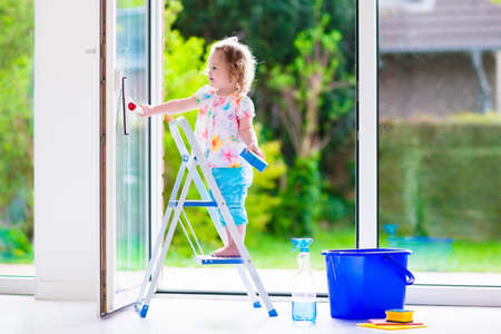 Photo pour Little girl washing a window. Kids clean the house. Children help at home. Toddler kid cleaning windows and doors standing on a ladder. Child helping with housework holding sponge and soap bottle. - image libre de droit