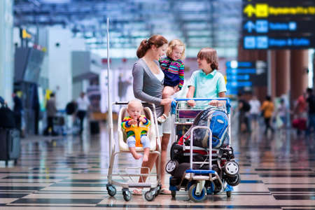 Foto de Family traveling with kids. Parents with children at international airport with luggage in a cart. Mother holding baby toddler girl and boy flying by airplane. Travel with child for summer vacation. - Imagen libre de derechos