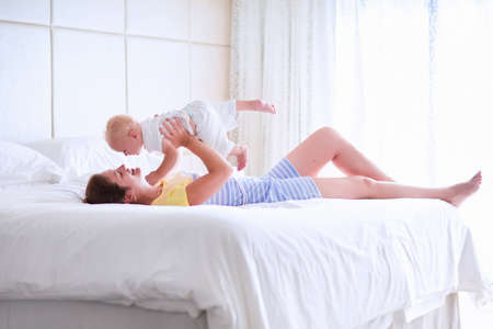Foto de Mother and baby in bed. Young mom playing with her newborn son. Child and parent together at home. Family with kids in the morning. Woman relaxing with kid in a sunny bedroom. Happiness and motherhood - Imagen libre de derechos