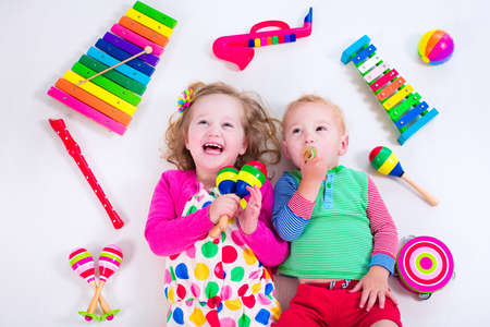 Photo for Child with music instruments. Musical education for kids. Colorful wooden art toys for kids. Little girl and boy play music. Kid with xylophone, guitar, flute. - Royalty Free Image