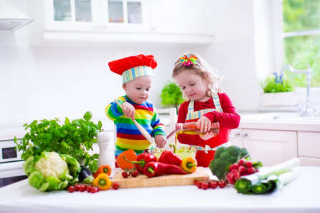 Foto de Kids cooking fresh vegetable salad in a white kitchen. Children cook vegetables for vegetarian lunch. Toddler and baby eat healthy dinner. Boy and girl preparing and eating raw meal. Child nutrition. - Imagen libre de derechos