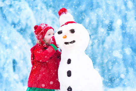 Photo pour Funny little toddler girl in a red knitted Nordic hat and warm coat playing with a snow. Kids play outdoors in winter. Children having fun at Christmas time. Child building snowman at Xmas. - image libre de droit