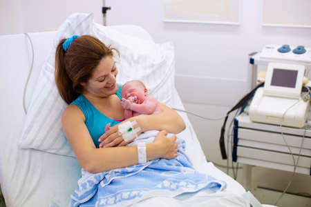 Photo pour Mother giving birth to a baby. Newborn baby in delivery room. Mom holding her new born child after labor. Female pregnant patient in a modern hospital. Parent and infant first moments of bonding. - image libre de droit