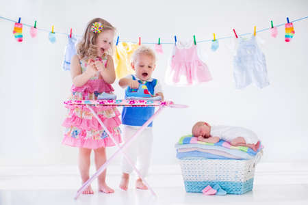Foto de Newborn child on pile of clean dry towels. Brother and sister playing with little sibling. Siblings bonding. Children ironing clothes. Twin kids play with baby boy. New born kid after bath in a towel - Imagen libre de derechos