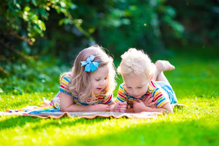 Photo pour Kids reading a book in summer garden. Children study. Boy and girl play in school yard. Preschool friends playing and learning. Siblings doing homework. Kindergarten kid and toddler read books. - image libre de droit