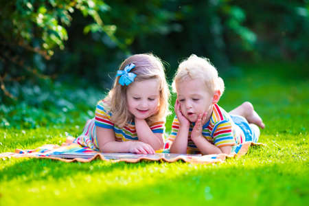 Foto de Kids reading a book in summer garden. Children study. Boy and girl play in school yard. Preschool friends playing and learning. Siblings doing homework. Kindergarten kid and toddler read books. - Imagen libre de derechos