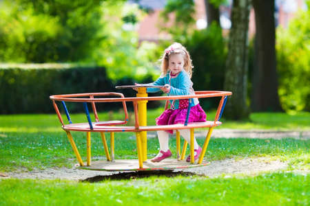 Photo for Little girl on a playground. Child playing outdoors in summer. Kids play on school yard. Happy kid in kindergarten or preschool. Children having fun at daycare play ground. Toddler on a slide. - Royalty Free Image