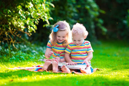 Photo for Kids reading a book in summer garden. Children study. Boy and girl play in school yard. Preschool friends playing and learning. Siblings doing homework. Kindergarten kid and toddler read books. - Royalty Free Image