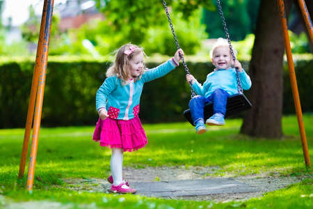 Photo for Little boy and girl on a playground. Child playing outdoors in summer. Kids play on school yard. Happy kid in kindergarten or preschool. Children having fun at daycare play ground. Toddler on a swing. - Royalty Free Image