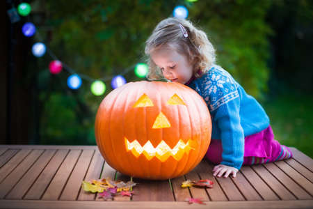 Photo for Little girl carving pumpkin at Halloween. Dressed up child trick or treating. Kids trick or treat. Child in witch costume playing in autumn park. Toddler kid with jack-o-lantern. - Royalty Free Image