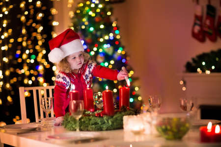 Foto de Christmas dinner at home. Child lighting a candle on advent wreath on Xmas eve. Decorated living room with fireplace and tree. Winter evening at fire place for family with kids. Children celebrating. - Imagen libre de derechos
