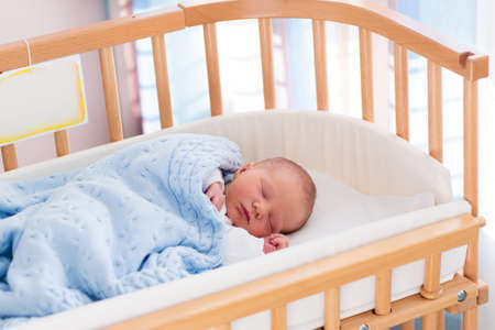 Photo pour Newborn baby in hospital room. New born child in wooden co-sleeper crib. Infant sleeping in bedside bassinet. Safe co-sleeping in a bed side cot. Little boy taking a nap under knitted blanket. - image libre de droit