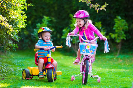 Photo pour Kids riding bikes in a park. Children enjoy bike ride in the garden. Girl on a bicycle and little boy on a tricycle in safety helmet playing together outdoors. Preschool child and toddler kid biking. - image libre de droit