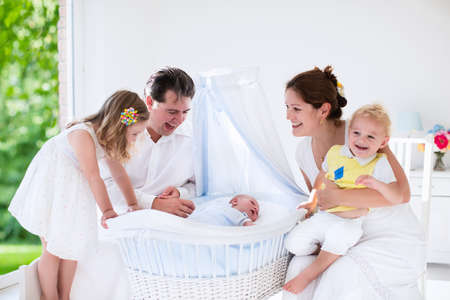 Big family with four kids in white bedroom. Parents and kids standing at crib of newborn baby boy. Mother and playing with new born child in moses basket. Kids meeting new sibling. Nursery for infant.