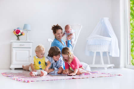 Photo pour Mother and children play indoors. Family with kids in a white bedroom. Mom with baby, boy and girl playing and reading books at home. Beautiful nursery for baby and toddler. Room for preschool child. - image libre de droit