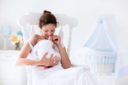 Photo pour Young mother holding her newborn child. Mom nursing baby. Woman and new born boy relax in a white bedroom with rocking chair and blue crib. Nursery interior. Mother breast feeding baby. Family at home - image libre de droit