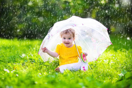 Little girl with colorful umbrella playing in the rain. Kids play outdoors by rainy weather in fall. Autumn outdoor fun for children. Toddler kid outside in the garden. Baby enjoying summer shower.