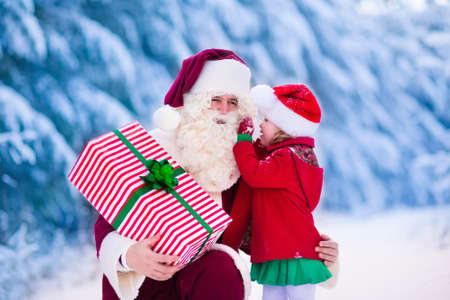 Photo for Santa Claus and children opening presents in snowy forest. Kids and father in Santa costume and beard open Christmas gifts. Little girl helping with present sack. Xmas, snow and winter fun for family. - Royalty Free Image