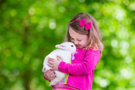 Photo for Children play with real rabbit. Laughing child at Easter egg hunt with white pet bunny. Little toddler girl playing with animal in the garden. Summer outdoor fun for kids with pets. - Royalty Free Image