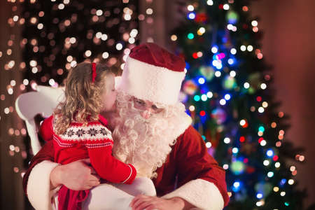Photo for Santa Claus and children opening presents at fireplace. Kids and father in Santa costume and beard open Christmas gifts. Little girl helping with present sack. Family under Xmas tree at fire place. - Royalty Free Image