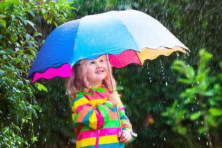 Little girl with colorful umbrella playing in the rain. Kids play outdoors by rainy weather in fall. Autumn fun for children. Toddler kid in raincoat and boots walking in the garden. Summer shower.