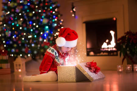 Photo for Family on Christmas eve at fireplace. Kids opening Xmas presents. Children under Christmas tree with gift boxes. Decorated living room with traditional fire place. Cozy warm winter evening at home. - Royalty Free Image
